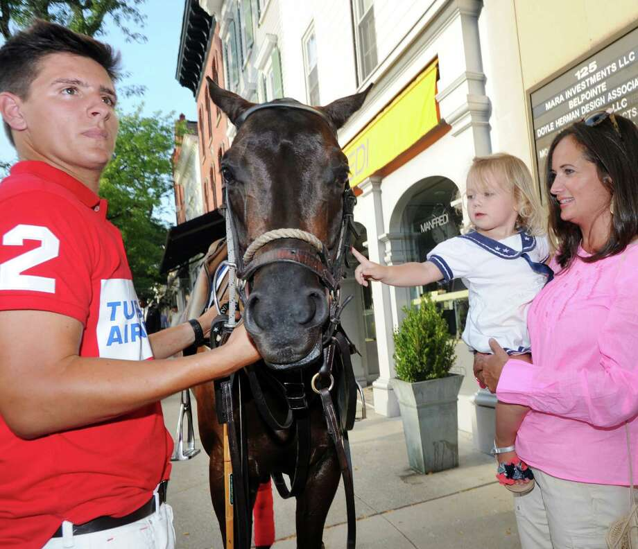Jones Glenn, 2, of Greenwich, is held by her mother Jen Danzi, while petting, Margarita, the horse of polo player Joaquin Panelo, left, of the Turkish Airlines Polo Team during a polo promotional event at the Shreve Crump & Low Jewelry store, 125 Greenwich Ave., Greenwich, Conn., Wednesday night, Aug. 19, 2015. The players and ponies along with officials from the United States Polo Association were promoting the East Coast Open Polo Championship that begins this Sunday at the Greenwich polo Club. Photo: Bob Luckey Jr., Hearst Connecticut Media / Greenwich Time