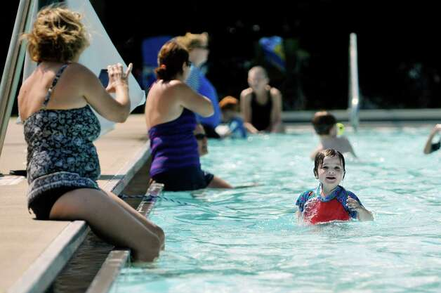 Maureen Pagano, left, of Albany, takes a video of her granddaughter, Hadley Thorpe, 3, swimming at the Elm Avenue Park pool complex on Wednesday, Aug. 19, 2015, in Delmar, N.Y.  Thorpe had been playing with some older children and learned some new swimming techniques from them and was showing them to her grandmother.  (Paul Buckowski / Times Union)