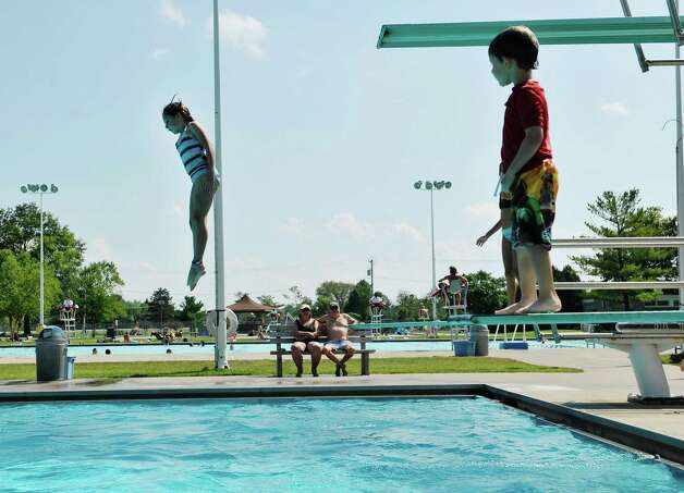 Penelope Rice, left, from East Hampton, Mass,  jumps off the high-dive board at the Elm Avenue Park pool complex on Wednesday, Aug. 19, 2015, in Delmar, N.Y.  Rice is in town visiting her grandparents.  (Paul Buckowski / Times Union)