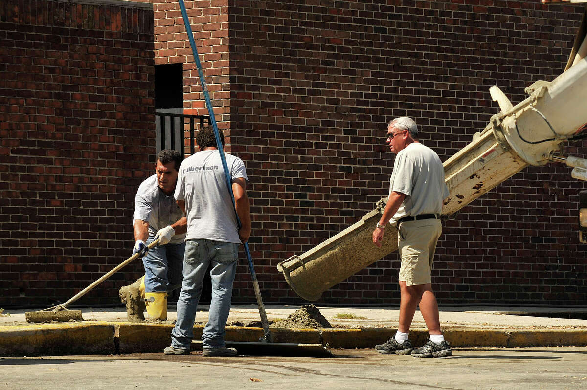 Rich Lyons, right, looks on as construction continues on a sidewalk outside Stamford High School in Stamford, Conn., on Wednesday, Aug. 19, 2015.