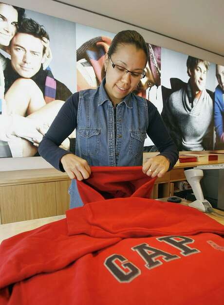 A Gap employee  arranges retail stock before the store opens in Palo Alto, Calif. Gap and Microsoft are among companies that have done away with the traditional performance reviews. Photo: Bloomberg News File Photo