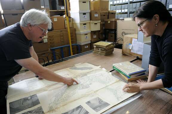 Rick and Megan Prelinger look at a historical map by the Weber Foundation Study that planned to dam and dyke off San Francisco Bay,  at the Prelinger Archive Library in San Francisco, CA Wednesday, August 19, 2015.