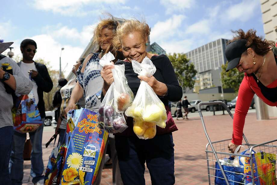 Bishop Swing Community Housing resident Jovita Zamora smiles as she show's off the produce she was able to buy with $5 at the farmer's market at U.N. Plaza in San Francisco, CA Wednesday, August 19, 2015.  Samuel Merritt UniversityÕs School of Nursing students Amy Stevenson  and Jennifer Lee created a free five-week Òhealthy eatingÓ course for SRO residents that culminates in a field trip to the farmerÕs market in U.N. Plaza, where they give the residents $5 to buy as much food as they can and then show them how to cook it. Photo: Michael Short, Special To The Chronicle