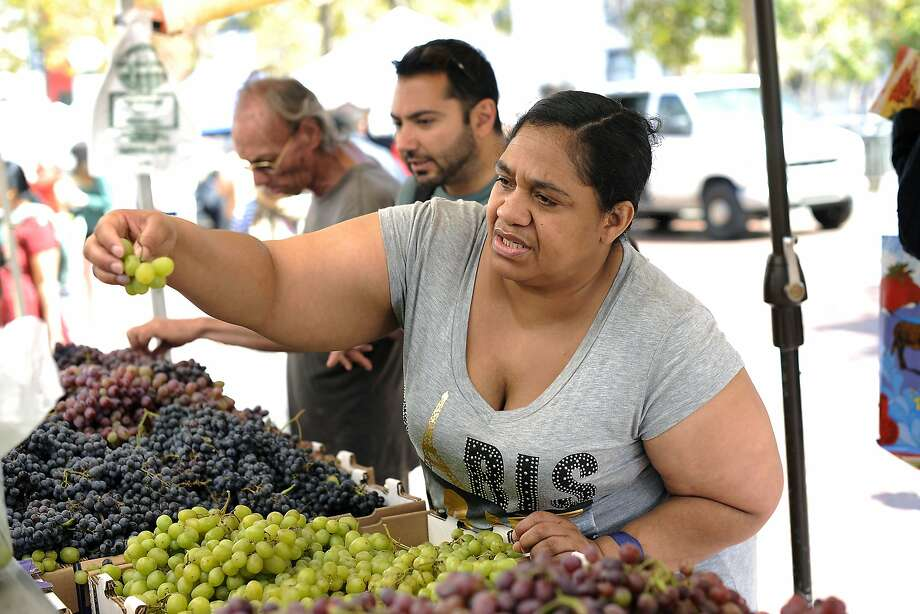 Bishop Swing Community Housing resident Linda Jones shops for grapes at the farmer's market at U.N. Plaza in San Francisco, CA Wednesday, August 19, 2015.  Samuel Merritt UniversityÕs School of Nursing students Amy Stevenson  and Jennifer Lee created a free five-week Òhealthy eatingÓ course for SRO residents that culminates in a field trip to the farmerÕs market in U.N. Plaza, where they give the residents $5 to buy as much food as they can and then show them how to cook it. Photo: Michael Short, Special To The Chronicle