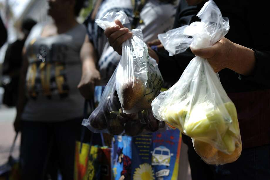 Bishop Swing Community Housing residents hold bags of produce they bought at the farmer's market at U.N. Plaza in San Francisco, CA Wednesday, August 19, 2015.  Samuel Merritt UniversityÕs School of Nursing students Amy Stevenson  and Jennifer Lee created a free five-week Òhealthy eatingÓ course for SRO residents that culminates in a field trip to the farmerÕs market in U.N. Plaza, where they give the residents $5 to buy as much food as they can and then show them how to cook it. Photo: Michael Short, Special To The Chronicle