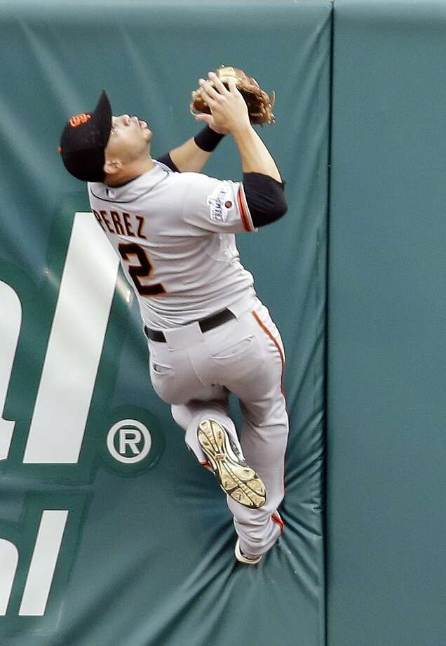 San Francisco Giants center fielder Juan Perez climbs the outfield wall to catch a ball hit by St. Louis Cardinals' Stephen Piscotty for an out during the first inning of a baseball game Wednesday, Aug. 19, 2015, in St. Louis. (AP Photo/Jeff Roberson) Photo: Jeff Roberson, Associated Press