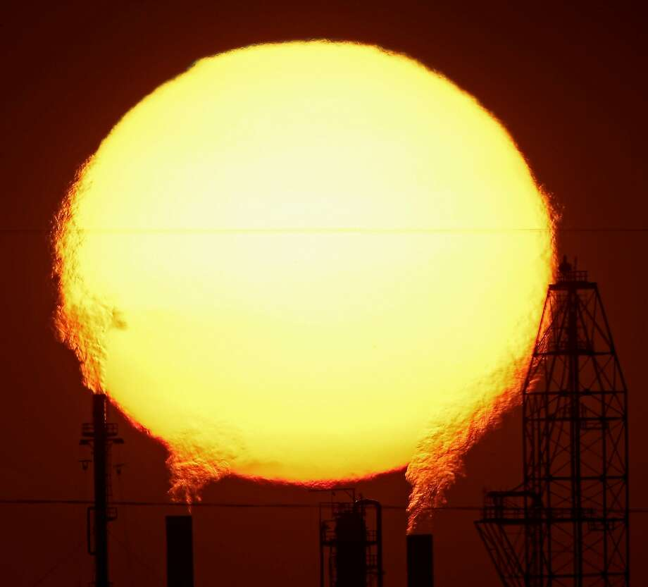 The sun sets behind the National Cooperative Refinery Association oil refinery Wednesday, Aug. 19, 2015, in McPherson, Kan.  Photo: Charlie Riedel, Associated Press
