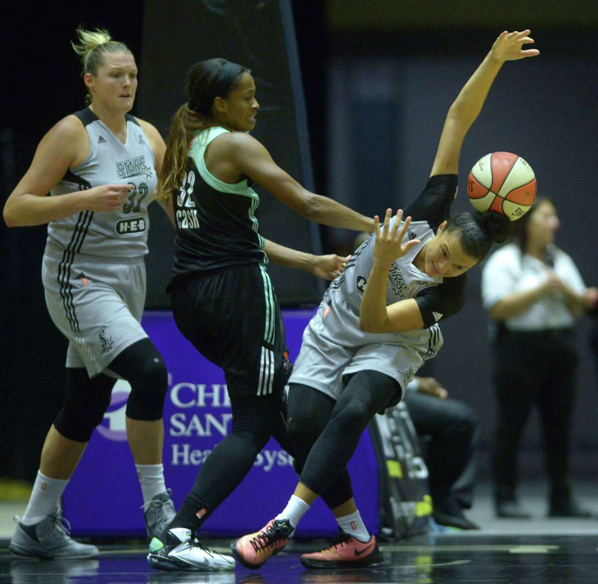 Kayla McBride of the San Antonio Stars looks for the loose ball as teammate Jayne Appel, left, and Swin Cash of the New York Liberty stand by during WNBA action at Freeman Coliseum on Wednesday, Aug. 19, 2015.
