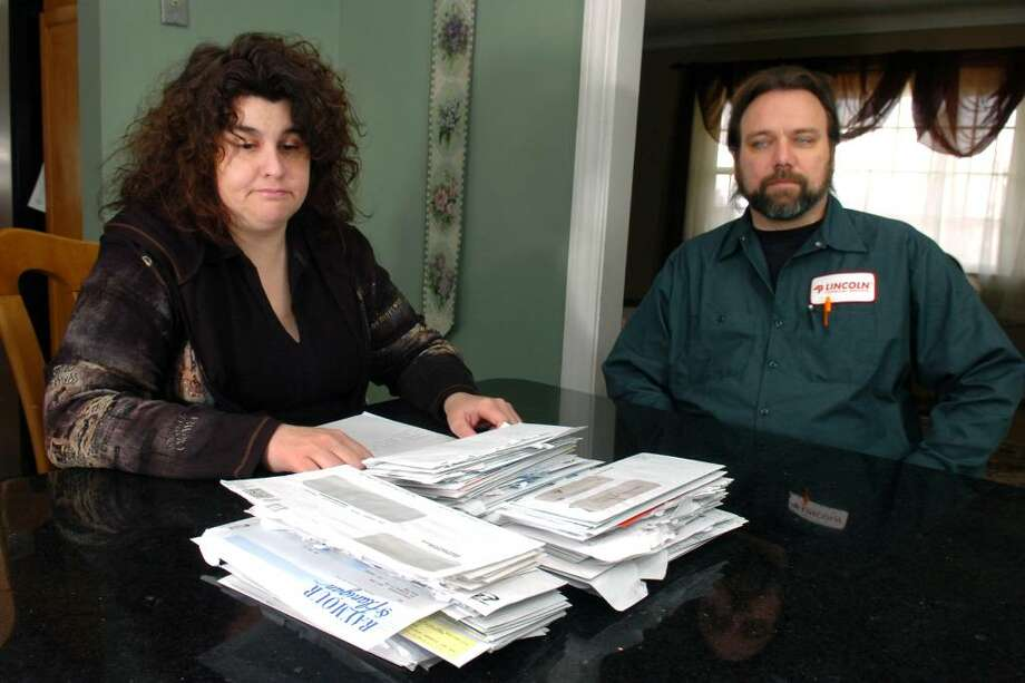 Karen Haight Selling and her husband Chris Selling pose with a pile of bills in their Shelton, Conn. home March 10th, 2010. Photo: Ned Gerard / Connecticut Post