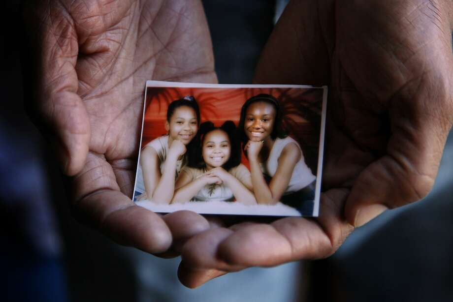 Walter Turner holds a photo of his daughter Naja Turner (left) and granddaughters Jayde Davis and Jasmine Turner, taken in late 2005 or early 2006 when the granddaughters lived with him during the aftermath of Hurricane Katrina. Photo: Nicole Fruge, The Chronicle