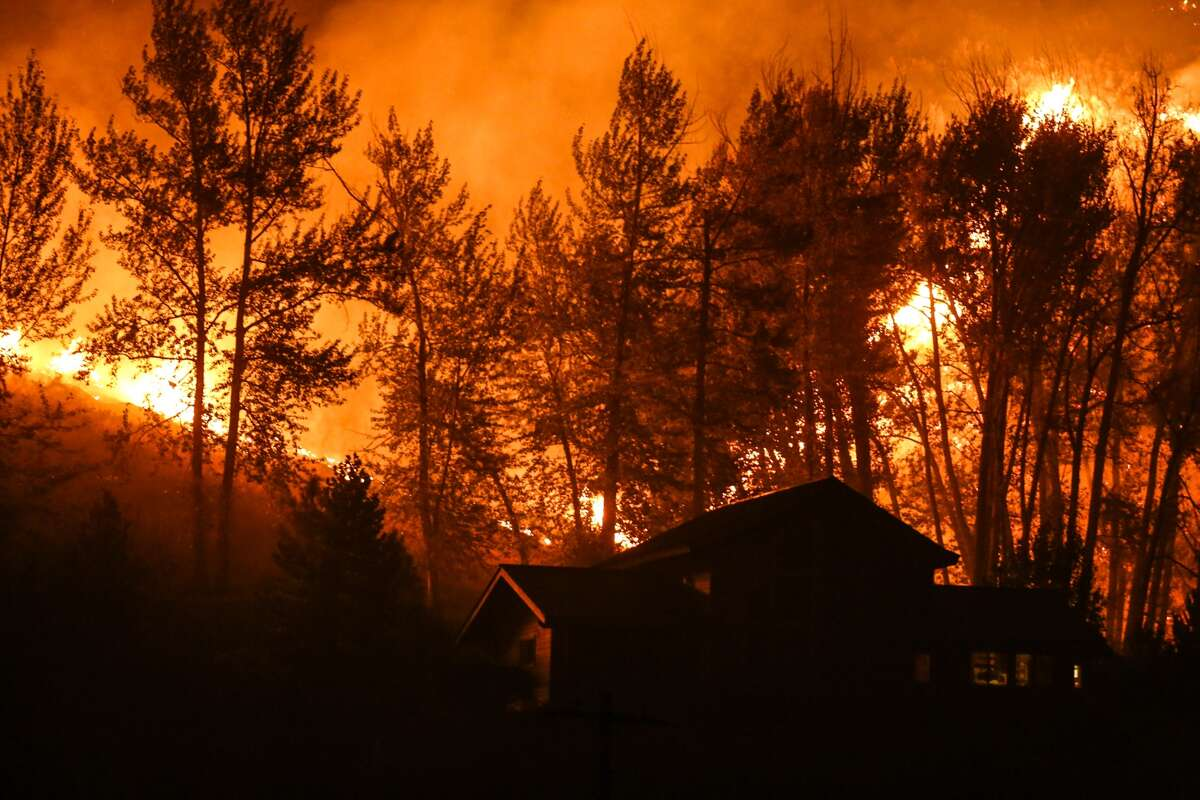 Fire approaches a house on Twisp River Road as flames advance on the town of Twisp.
