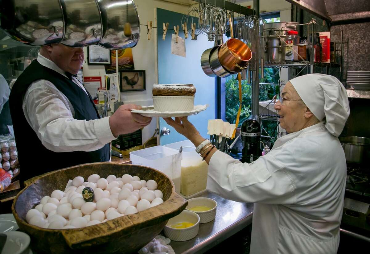 Chef Jacqueline Margulis hands a chocolate soufflé to server Scott Unger at Cafe Jacqueline in San Francisco