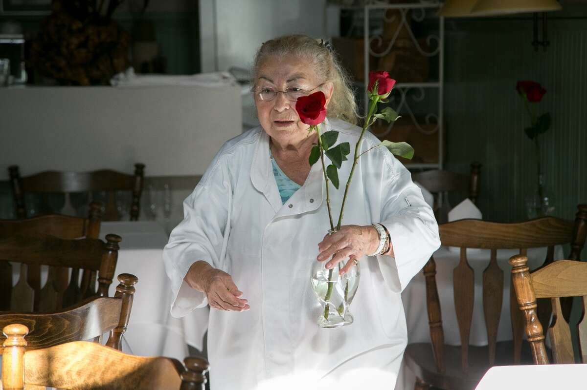 Chef Jacqueline Margulis places flowers on the tables before service