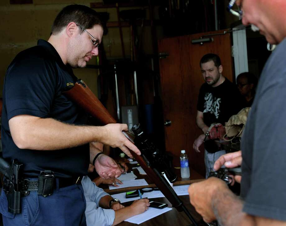 Bridgeport Police Sgt. Luigi Tucciarone, left, and Officer Pete Garcia log weapons brought in during Bridgeport's Gun Buyback initiative Saturday, July 18, 2015, at the Police Department Community Services Division at 1395 Sylvan Ave. The Bridgeport Police Department offered up to $200 for a working handgun, up to $100 for a rifle and a weapon determined to be an assault rifle was eligible for up to $400. Photo: Autumn Driscoll / Hearst Connecticut Media / Connecticut Post