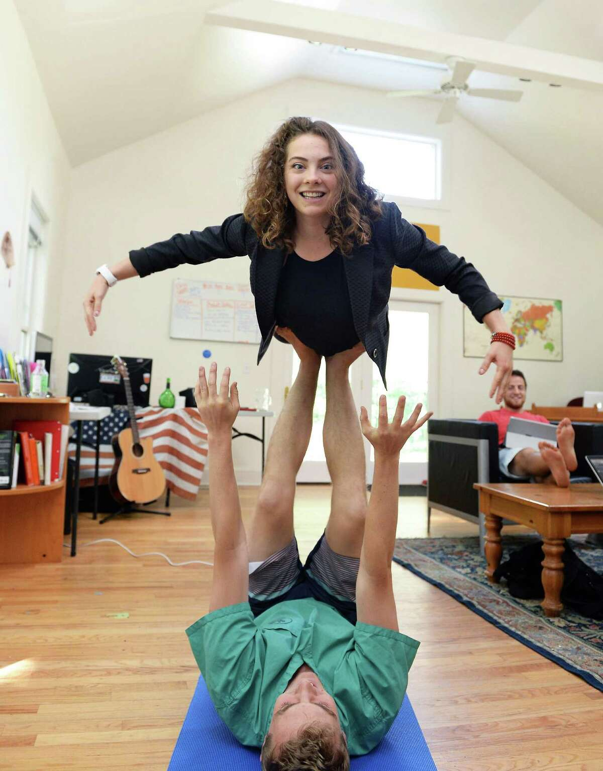 Ant Hill CEO Marcella Jewell ?flies? with the help of a coworker in the main office space of their Hacker House, where young entrepreneurs live and work. Jewell often uses yoga and gymnastics as part of her creative process. (John Carl D'Annibale / Times Union)