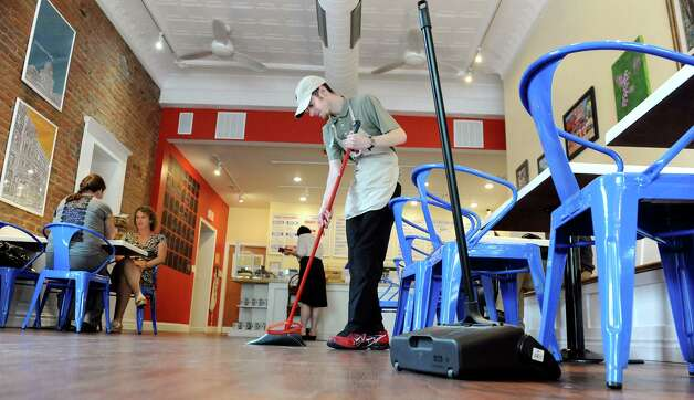 Employee Tim Primeau sweeps the floor. ?Puzzles is open from breakfast ?through dinner to maximize business ?and available shifts for workers. (Cindy Schultz / Times Union) Photo: Cindy Schultz / 00032293A