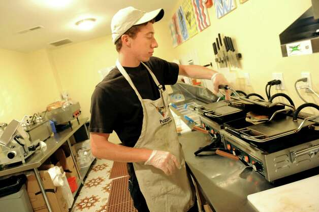 Employee Bryan Bidwell, 19, places a sandwich on the grill on Tuesday, June 16, 2015, at Puzzles Bakery and Cafe in Schenectady, N.Y. (Cindy Schultz / Times Union) Photo: Cindy Schultz / 00032293A