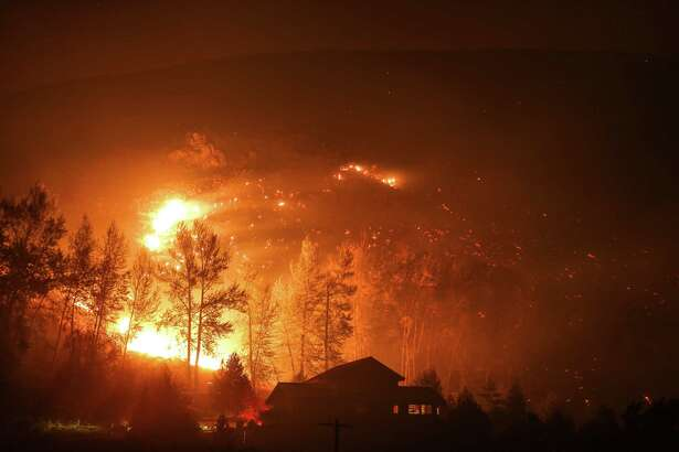 A wildfire closes in on a house on Twisp River Road in Twisp, Wash. The fire spared the house. Three firefighters were killed nearby in the inferno. Photographed on Thursday, August 20, 2015.