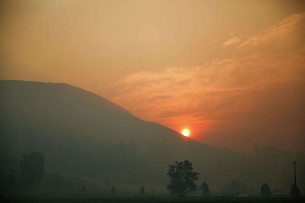 The sun rises over the Twisp River valley after a wildfire tore through the hills around Twisp, Wash. Three firefighters were killed in the inferno. Photographed on Thursday, August 20, 2015.