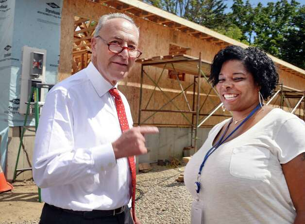 Sen. Charles Schumer, left, and home owner Karena Blackmon in front of Blackman's home being rebuilt by Habitat for Humanity of Schenectady County, using HOME Program funding on Carrie St. Thursday August 20, 2015 in Schenectady, NY.  Sen. Schumer has launched a push to fight steep funding cuts that have been proposed in the Senate Transportation, Housing and Urban Development (THUD) Appropriations bill that would negatively impact Schenectady and other Capital Region communities.  (John Carl D'Annibale / Times Union)(John Carl D'Annibale / Times Union) Photo: John Carl D'Annibale