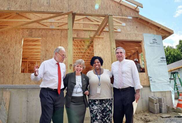 Sen. Charles Schumer, left, Schenectady Habitat's Madelyn Thorne, home owner Karena Blackmon and Schenectady Mayor Gary McCarthy, right, tour homes being rebuilt by Habitat for Humanity of Schenectady County, using HOME Program funding on Carrie St. Thursday August 20, 2015 in Schenectady, NY.  (John Carl D'Annibale / Times Union)(John Carl D'Annibale / Times Union) Photo: John Carl D'Annibale