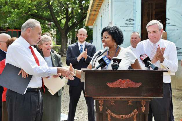 Sen. Charles Schumer, left, with home owner Karena Blackmon and Schenectady Mayor Gary McCarthy, right, during a news conference in front of homes being rebuilt by Habitat for Humanity of Schenectady County, using HOME Program funding on Carrie St. Thursday August 20, 2015 in Schenectady, NY.  (John Carl D'Annibale / Times Union)(John Carl D'Annibale / Times Union) Photo: John Carl D'Annibale