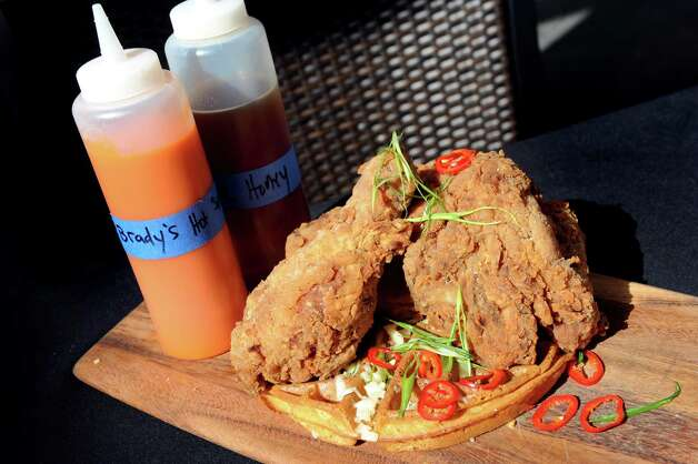 Signature Chicken and Waffles features free-range chicken, on top of a cheddar, scallion and jalapeno waffle served with house hot sauce and local honey on Thursday, Aug. 13, 2015, at The Patio at 15 Church in Saratoga Springs, N.Y. (Cindy Schultz / Times Union) Photo: Cindy Schultz / 00032979A