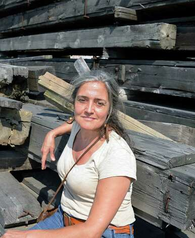 Camille Gibeau with reclaimed wooden beams at Silver Fox Salvage Friday August 14, 2015 in Albany, NY.  (John Carl D'Annibale / Times Union) Photo: John Carl D'Annibale / 00033008A