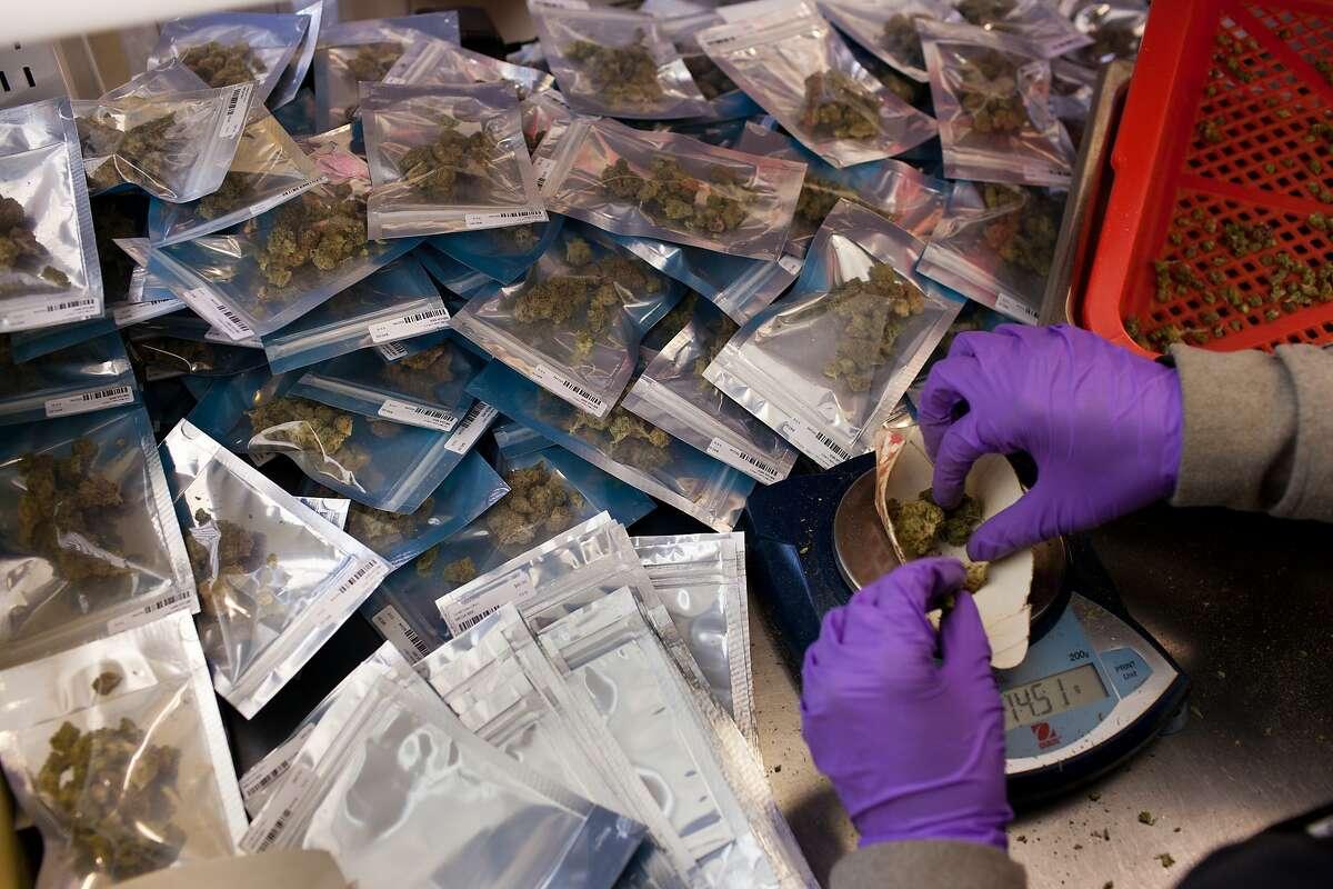 Angela Grasty weighs and packages medical marijuana at Harborside Health Center in Oakland, Calif. on Thursday, June 5, 2014.