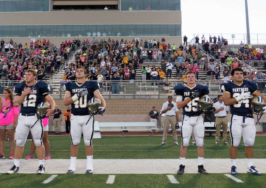 FILE: O'Connor players Kody Fields (from left), Michael Kurfehs, Zach Millington and Miguel Martinez pay their respects during the playing of the national anthem at Farris Stadium on Saturday, Oct. 18, 2014. Photo: Billy Calzada /San Antonio Express-News / San Antonio Express-News