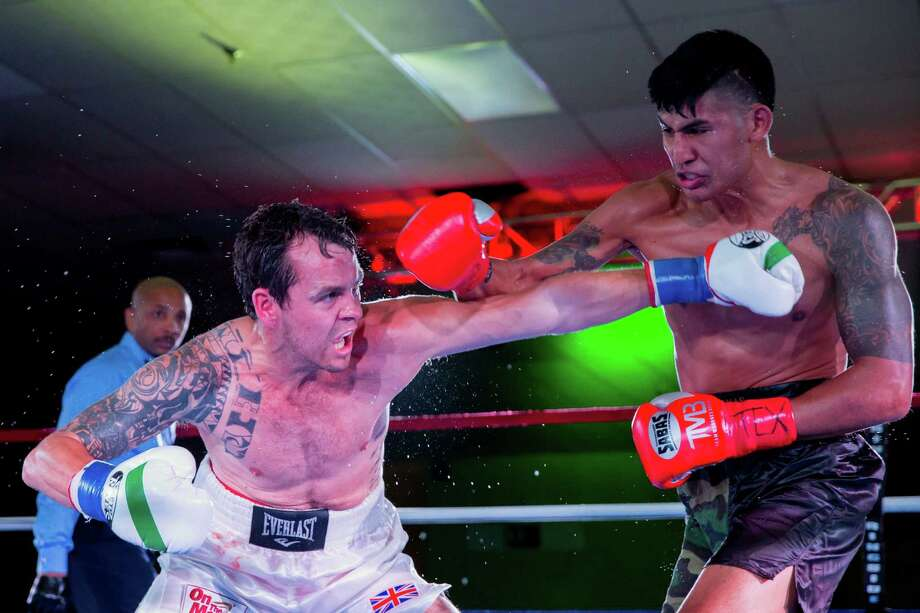 Steven Hall (left) ducks under a punch from Armando Cardenas during their boxing match on Aug. 8, 2015, at the San Antonio Event Center. Hall won on a late knockout. Photo: Mario Rojas /Courtesy Photo