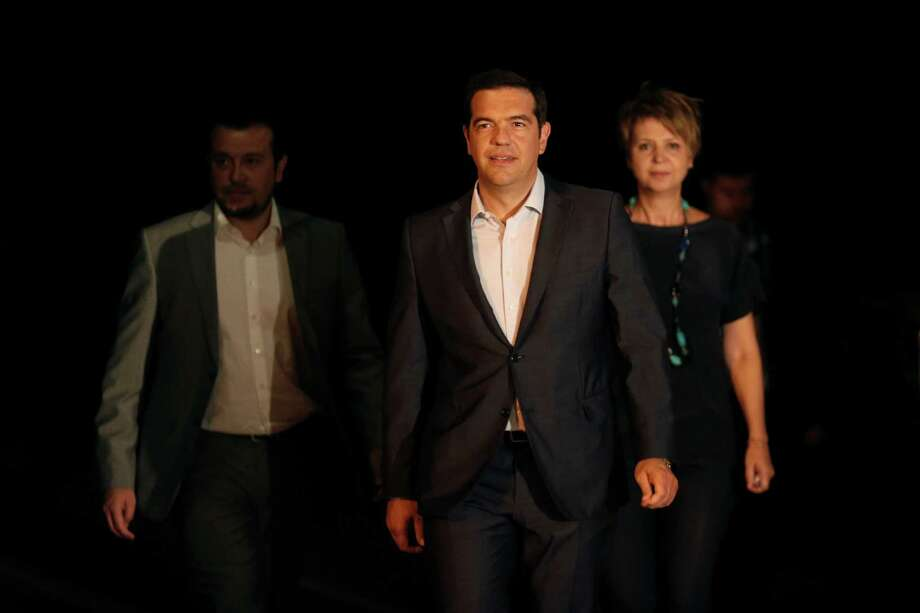 Greek Prime Minister Alexis Tsipras, center, leaves the Presidential palace after a meeting with Greek President Prokopis Pavlopoulos, in Athens, on Thursday, Aug. 20, 2015. Tsipras announced his government's resignation and called early elections Thursday, seeking to consolidate his mandate to implement a new three-year international bailout that sparked a rebellion within his radical left Syriza party. (AP Photo/Petros Giannakouris) Photo: Petros Giannakouris, STR / AP