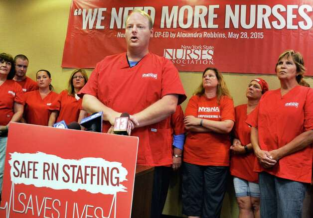 Ellis Medicine ER nurse Fred Durocher, center, speaks during a news conference where registered nurses at Ellis Medicine, members of the New York State Nurses Association, issue a 10-day-notice to strike Thursday August 20, 2015 in Schenectady, NY.  (John Carl D'Annibale / Times Union) Photo: John Carl D'Annibale / 00033058A