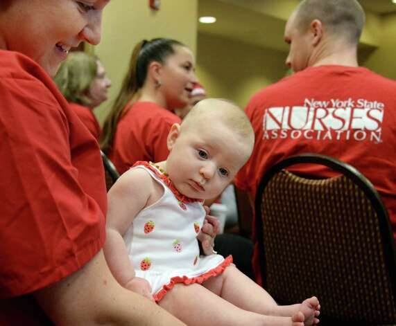 Ellis Medicine RN Bridget Yawarski, left, holds her 6-month-old daughter Ellie during a news conference where registered nurses at Ellis Medicine, members of the New York State Nurses Association, issue a 10-day-notice to strike Thursday August 20, 2015 in Schenectady, NY.  (John Carl D'Annibale / Times Union) Photo: John Carl D'Annibale / 00033058A