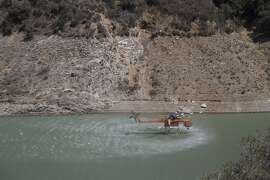 AZUSA, CA - AUGUST 15:  A firefighting helicopter draws from the lower than normal waters of the San Gabriel Reservoir while fighting the Cabin Fire in the Angeles National Forest on August 15, 2015 north of Azusa, California. The fire has grown to 2,500 acres with 0 percent containment under heat wave conditions.  (Photo by David McNew/Getty Images)