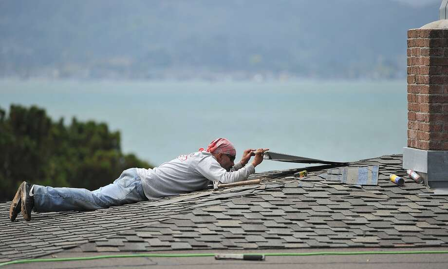 Pedro Carreno of ARS Roofing works on a home in Tiburon that is being weatherproofed ahead of the now-likely wet and heavy storms expected to arrive in the Bay Area this winter. Photo: Josh Edelson, JOSH EDELSON / SAN FRANCISCO CHR