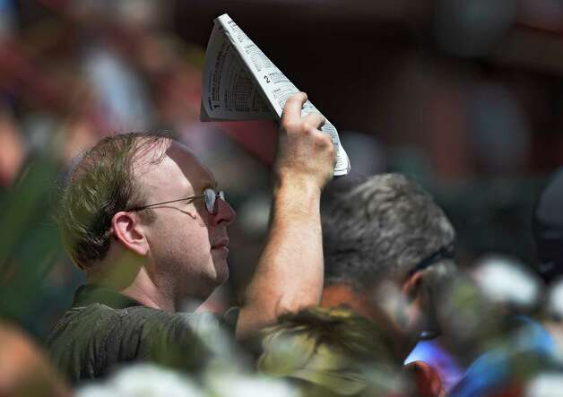 A racing patron uses his race card to shield his eyes from the sun during racing on the main track at the Saratoga Race course Thursday afternoon Aug. 20, 2015 after morning exercise  in Saratoga Springs, N.Y.    (Skip Dickstein/Times Union) Photo: SKIP DICKSTEIN