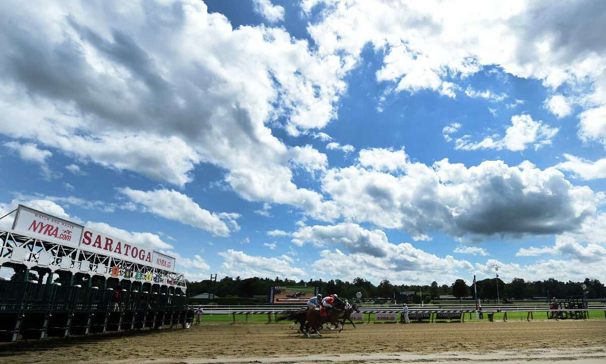 The first race breaks from the gate under a heavy cloud formation during racing on the main track at the Saratoga Race course Thursday afternoon Aug. 20, 2015 after morning exercise in Saratoga Springs, N.Y. The weather is expected to decline in quality and heavy rains are forecast for late tonight in to tomorrow morning. (Skip Dickstein/Times Union)
