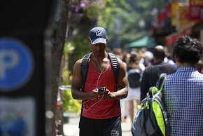 A cellphone user near the campus of the University of California, Berkeley, in Berkeley, Calif., July 7, 2015. A city measure requiring retailers to warn cellphone customers about radiation exposure is on hold pending a lawsuit from the wireless industry. (Jim Wilson/The New York Times)