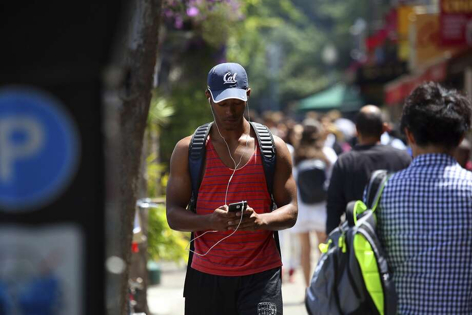 A cell phone user near the campus of the University of California, Berkeley, in Berkeley, Calif., July 7, 2015. A city measure requiring retailers to warn cell phone customers about radiation exposure is on hold pending a lawsuit from the wireless industry. (Jim Wilson/The New York Times) Photo: Jim Wilson, New York Times
