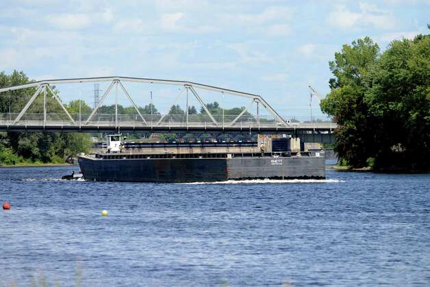 An empty barge heads south on the Hudson River in Mechanicville as work on General Electric's ongoing PCB remediation in the upper Hudson continues Thursday afternoon, Aug. 20, 2015, in Mechanicville, N.Y. GE said it has cost more than $1 billion to field a flotilla of dredges and barges as well as build the treatment plant. Between 1947 and 1977, GE dumped 1.3 million pounds of PCBs into the Hudson from capacitor plants in Hudson Falls and Fort Edward. (Will Waldron/Times Union) Photo: WW