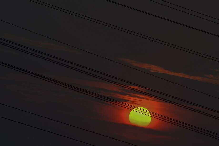 A sunset is seen past high-voltage electric power transmission lines in Kuala Lumpur on August 20, 2015. Photo: Mohd Rasfan, AFP / Getty Images