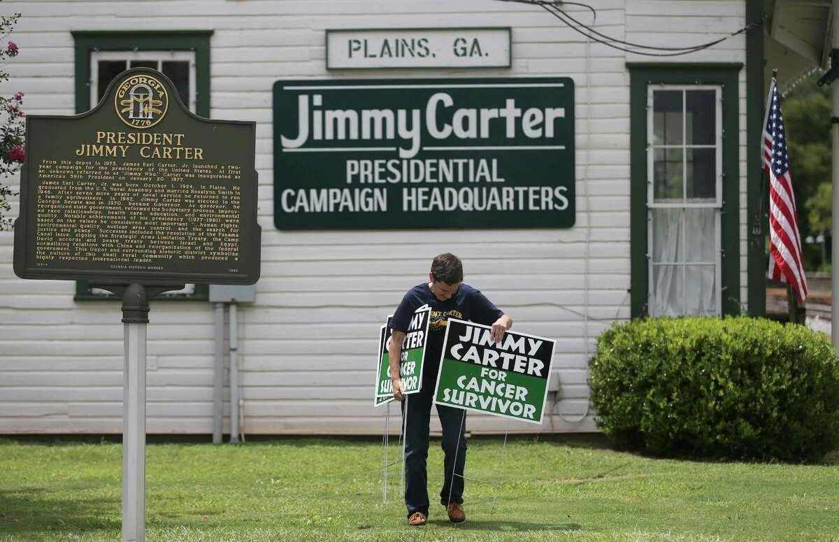 """Jill Stuckey places """"Jimmy Carter for Cancer Survivor"""" signs in Plains, Ga., Thursday in advance of the former president's return to his hometown."""
