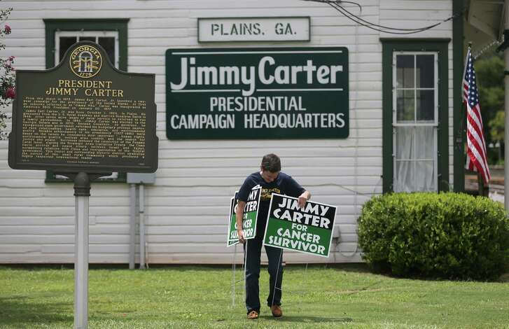 "Jill Stuckey places ""Jimmy Carter for Cancer Survivor"" signs in Plains, Ga., Thursday in advance of the former president's return to his hometown."