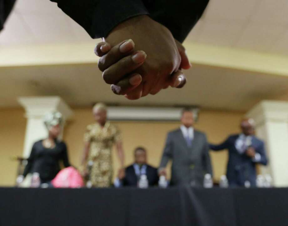 Attendees hold hands as Bishop James Dixon leads a prayer to close a town hall meeting on the conduct of troopers at Community of Faith church on Thursday. Photo: Jon Shapley, Houston Chronicle / © 2015 Houston Chronicle