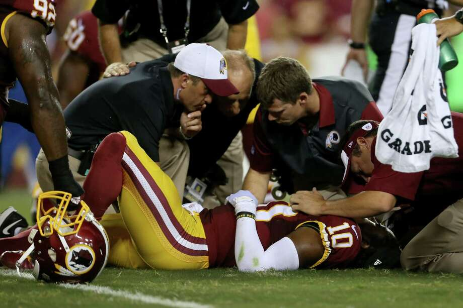 Quarterback Robert Griffin III is examined after fumbling in Thursday night's game against the Lions. He suffered a concussion and hurt his right shoulder. Photo: Matt Hazlett, Stringer / 2015 Getty Images