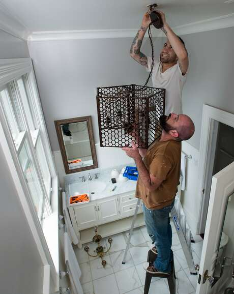 Zaque Eyn (below) and Andy Mandel (above) of Gigi Park install a light fixture at a home being prepped for sale in San Francisco on Thursday, August 20, 2015. Many home sellers are waiting to list their homes until September; one of the hottest months of the year for real estate sales. (JOSH EDELSON / SPECIAL TO THE CHRONICLE) Photo: Josh Edelson, JOSH EDELSON / SAN FRANCISCO CHR