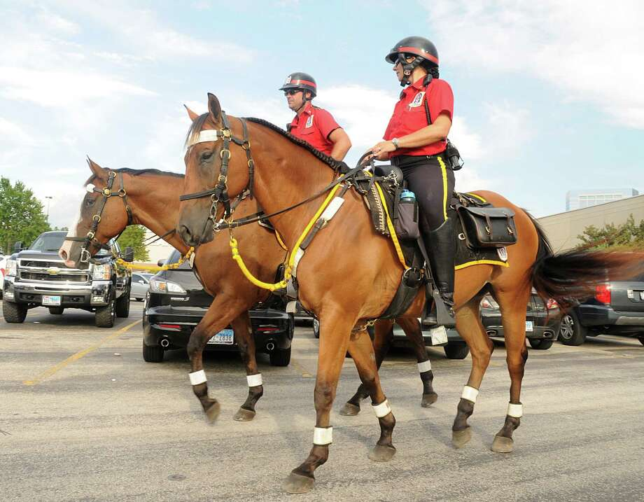 Cpl. Curtis Hillard and Trooper First Class Lori Williamson, both with Alpha & Omega Mounted Patrol, rode their horses in The Woodlands Mall parking lot. Photo: David Hopper, Freelance / Freelance
