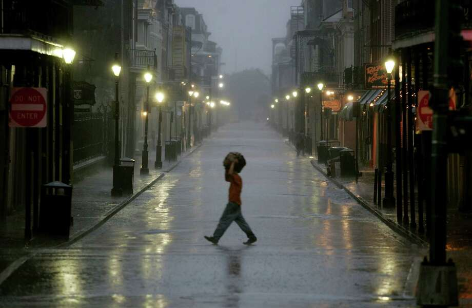 A man covers his head with a bag as he walked across a street in the French Quarter. Photo: Mark Wilson, Getty Images / Getty Images North America