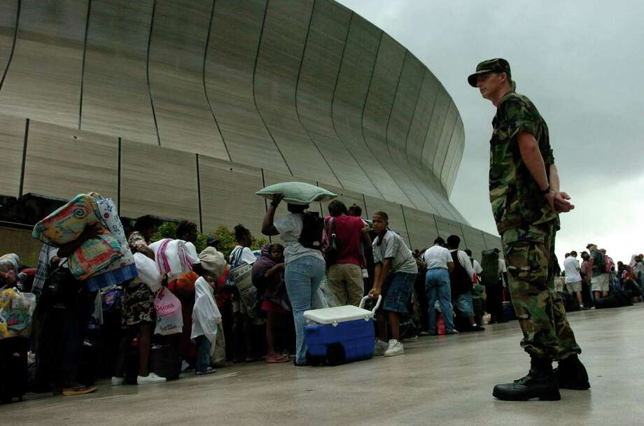 A Louisiana Air Guard member stands watch over a line as thousands of people waited to enter the Superdome before the arrival of Hurricane Katrina. Photo: MELISSA PHILLIP, HOUSTON CHRONICLE / HOUSTON CHRONICLE